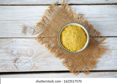 nutritional yeast flakes on wooden surface