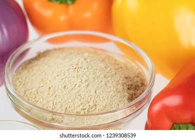 Nutritional yeast surrounded by other fresh ingredients for creamy vegan peppers and onions.