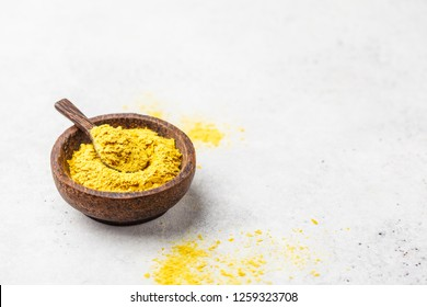 Nutritional yeast in a wooden bowl, copy space