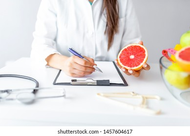 Nutritionist desk with healthy fruit, juice and measuring tape. Dietitian working on diet plan. Weight loss and right nutrition concept. Woman dietitian typing, counting calories or writing diet plan