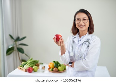 Nutritionist desk with healthy fruits, juice and measuring tape. Dietitian working on diet plan at office, smiling at camera. Weight loss and right nutrition concept
