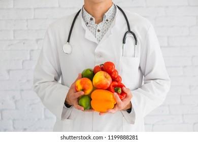 Nutritionist, doctor holding fresh fruit