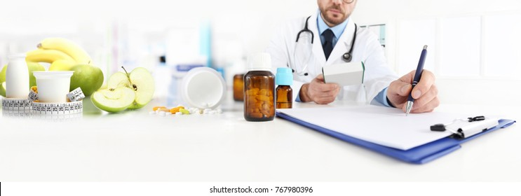 Nutritionist doctor writes the medical prescription for a correct diet on a desk with fruits, drugs and supplements, web banner and copy space template