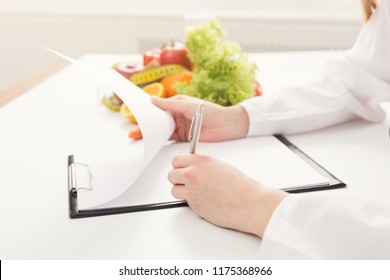 Nutritionist doctor writing diet plan on table. Unrecognizable dietitian making healthy eating menu, copy space for text, closeup. Right nutrition and slimming concept