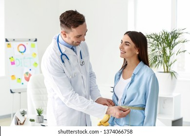 Nutritionist measuring waist of young woman in weight loss clinic