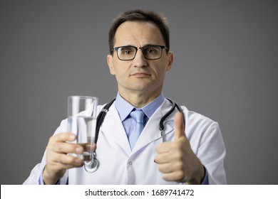 Nutritionist in white coat with a stethoscope on his neck holds a glass of water in his hands and points a finger at it. Healthy lifestyle. Thirst. Proper nutrition. Water-salt balance. Thumb up. Like