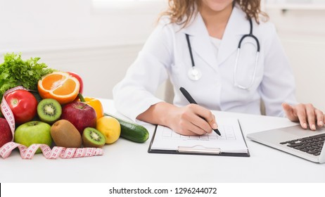 Nutritionist working in office. Doctor writing diet plan on table and using laptop, panorama, copy space