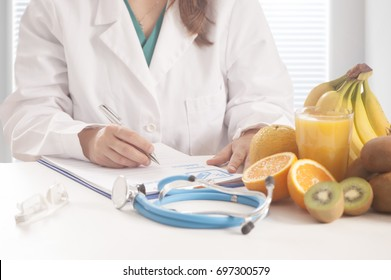 Nutritionist writing medical records and prescriptions with fresh fruits