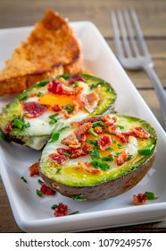 Nutritious breakfast of baked avocado egg boats with bacon crumbles and chives on white rectangle plate with whole wheat toast