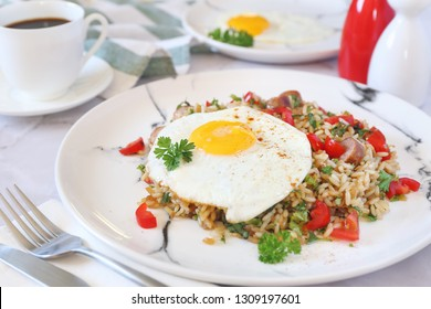 Nutritious breakfast. Spicy roast rice with red cherry tomatoes, sausages, fried eggs and cup of coffee