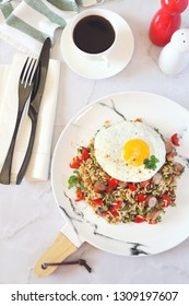 Nutritious breakfast. Spicy roast rice with red cherry tomatoes, sausages, fried eggs and cup of coffee. Top view