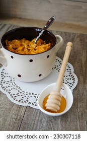 nutritious cereal cornflakes breakfast on the wooden table with honey and milk