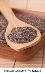 Nutritious chia seeds on a wooden spoon in a wooden bowl.