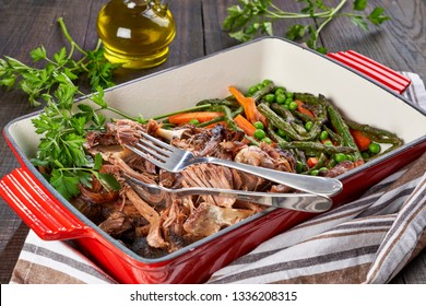 Nutritious full of protein pulled lamb meat with vegetables: green peas, carrots, asparagus in a red baking dish, vertical view on a wooden table with olive oil, fresh parsley stems, horizontal