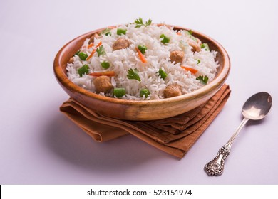 Nutritious Soybean pulao/Pilaf or Soya chunk fried Rice with green peas and beans. Served in a bowl over colourful or wooden background. Selective focus
