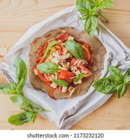 Nutritious vegan food. Wholewheat pancake with tomato, onion, basil and ajvar.