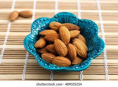 Nuts of almonds in a beautiful blue bowl, top view. Group of almonds. Peeled almonds. Pile of almonds. Almonds kernel.