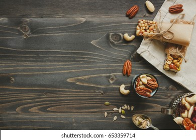 Nuts background. Healthy bars with nuts, seeds and dried fruits on the wooden table, with copy space.