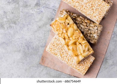 Nuts in caramel, honey on gray table background. Snack food. Unhealthy eating. Copy space, top view