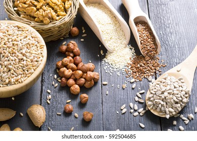 nuts and cereal seeds on black wood table background