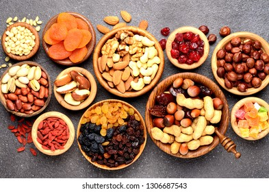 Nuts and dried fruits assortment on stone table - symbols of judaic holiday Tu Bishvat. Top view.