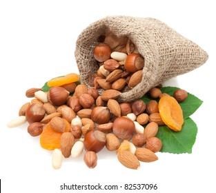nuts  and dried fruits in a linen basket on green leaves isolated on white background