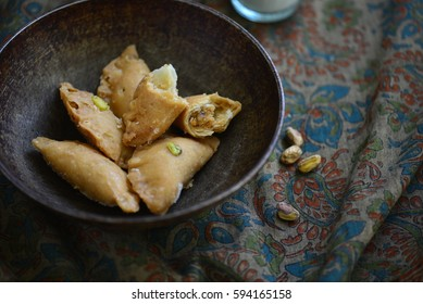 Nuts and khoya stuffed 'Gujhiya' presented in an old grunge bowl. Authentic sweet dumplings is a speciality of North India.