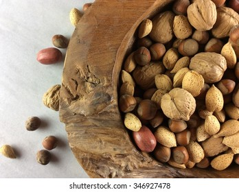 nuts in large wooden bowl on marble cutting board