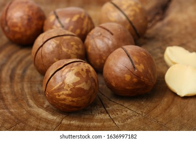 Nuts of Macadamia on wooden background.
