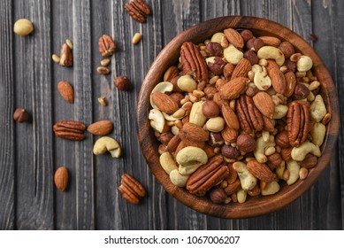 Nuts mix Almonds, Cashews, Macadamia, Peanuts, Walnuts, Pecans, Pine Nuts, Pistachios in a wooden plate