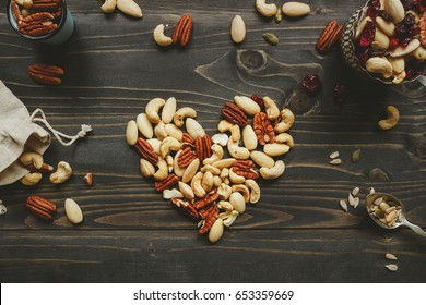 Nuts mix in heart shape on the wooden table. Nuts mix with seeds and dried fruits on the wooden table.