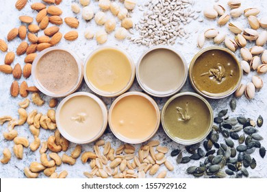Nuts and seeds butter in jars with ingredients. Homemade raw organic peanut, almond, hazlenut, cashew, pistachio, macadamia nuts paste and sunflower and pumpkin seeds butter on a table. Top view.
