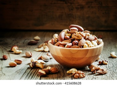 Nuts set in bowl almonds, pistachios, cashews, hazelnuts, peanuts, Brazil nuts, walnuts, vintage wooden background, focus vyboronchy