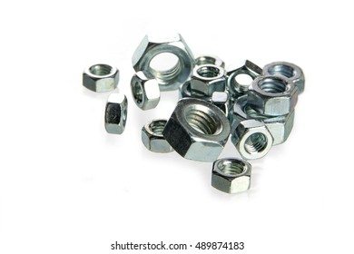 nuts of steel for machine screws on a heap isolated on a white background, concept for construction, crafts and industry, closeup with selected focus and narrow depth of field