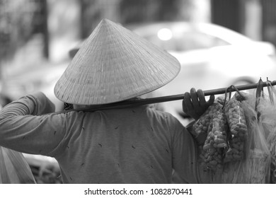 A nuts trader in a straw hat carries the goods on his shoulders. Vietnam