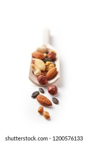 Nuts variation in a wooden spoon isolated on a white background. Almond, peanut, brazil nut, pumpkin seed, sunflower seed, cashew, hazelnut, walnut assortment. Top view