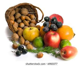 Nuts,walnuts,almonds,tangerine,apples and grapes scattered out from basket...