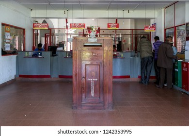 Nuwara Eliya, Sri Lanka - August 6, 2018: People at customer counters and a wooden letter box inside the post office building
