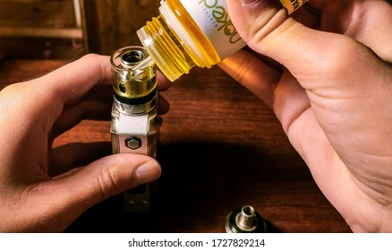 NY / USA - May 11, 2020: Naked brand flavored e-liquid vape juice being used to fill a vape mod