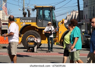 NYACK, NY - JULY 9, 2017: Street performer in front of a bulldozer on Broadway in Nyack.  Editorial use only.