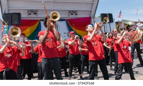 Nyack, NY - June 14 2015: Nyack High School Marching Band performing at Rockland County Pride 2015. Teens in red shirts play on trumpets and trombones with joy and enthusiasm.