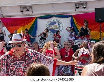 Nyack, NY - June 14 2015: Members of Batala NYC, women only band, with leader on the front performing during Rockland County Pride. Women before and on the stage express joy and enthusiasm.