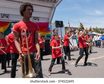 Nyack, NY - June 14 2015: Nyack High School Marching Band performing at Rockland County Pride 2015. Teens in red shirts are dancing, black boy at front is singing.