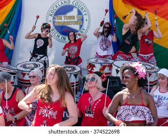 Nyack, NY - June 14 2015: Members of Batala NYC, women only band, performing on and before the stage during Rockland County Pride. Women smile, expressing joy and enthusiasm.