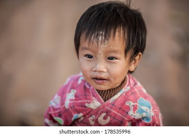 NYAUNG SHWE, MYANMAR - FEB 15: Unidentified kid uses Tanaka, a traditional burmese yellowish-white cosmetic paste made from the ground bark of the thanaka tree on Feb 15, 2014 in Nyaung Shwe, Myanmar.