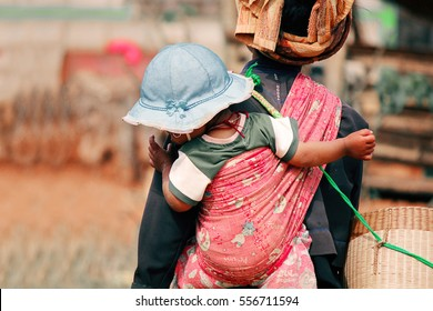 NYAUNG SHWE, MYANMAR - FEB 7, 2015: Mother carrying her child in the countryside in Myanmar