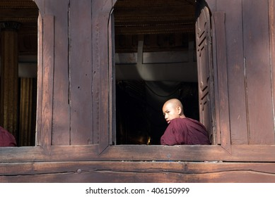 NYAUNG SHWE, MYANMAR, FEBRUARY 14, 2016: Two young novice buddhist monk are talking at a window of the Shwe Yaunghwe Kyaung monastery in Nyaung Shwe, Myanmar (Burma).