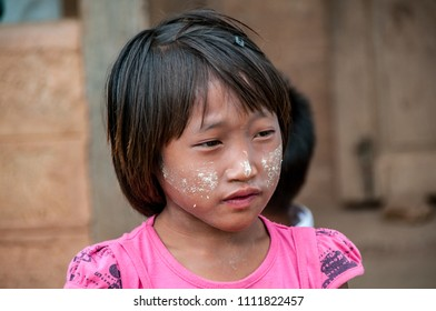 NYAUNG SHWE, MYANMAR - NOV 9, 2012 : close-up of children with Thanakha paste on their faces, at Nyaungshwe Inle Lake, November 9, 2012. Children will gladly pose for tourists' photos.