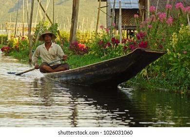 Nyaungshwe Township on Inle Lake / Burma (Myanmar) - December 4, 2012: Portrait of sitting Burmese man paddling a boat on lake