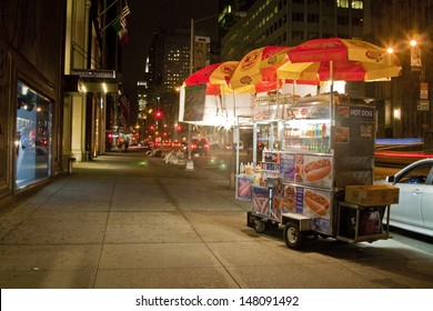 NYC - APRIL 29: A hot dog stand vendor stays open late into the night in New York City on April 29, 2013 in order to sell a few more hot dogs to late night passerbys.